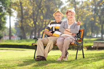 Mature couple relaxing seated on a bench in park