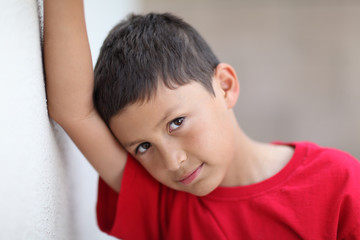 Serious young boy leans against wall