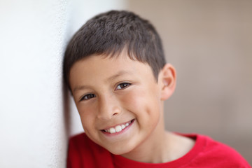 Smiling boy leaning against wall