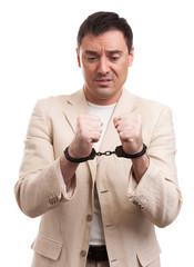 Worried caucasian business man in handcuffs