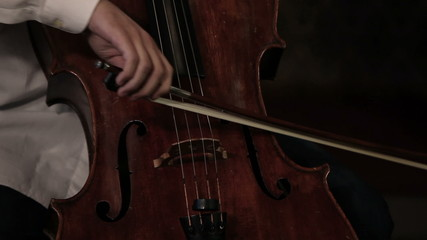 Close up pan shot of a cello player