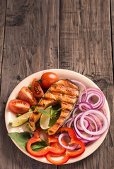 Grilled salmon steak with sliced onion and tomatoes vertical