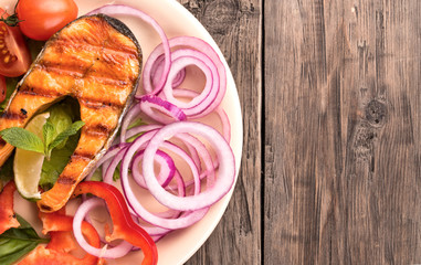 Grilled salmon steak with sliced onion and tomatoes at left