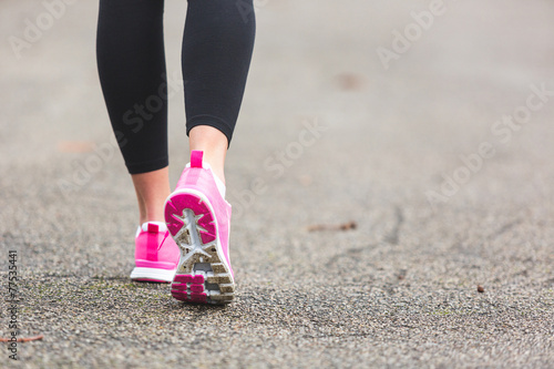 canvas print picture Female Runner Shoes closeup on the road, town setting.