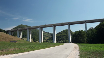 Cars driving over huge viaduct with view from below