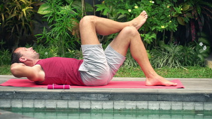 Young, handsome man doing twist sit-ups lying on mat in garden