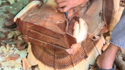 Hand of carver carving wood