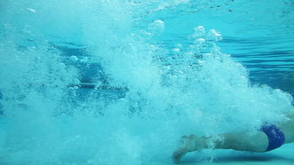 Girl jumping into a pool and swimming under water