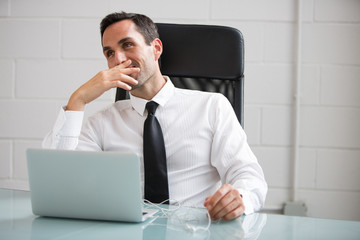 Male businessman with earphones and laptop
