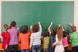 Group of nine children drawing on school chalkboard with chalks. - 77540434