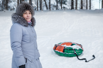 Mature woman standing near inflatable snow tube in winter forest