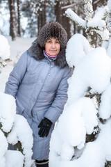 Caucasian woman portrait standing near pine snowy branches