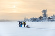 Winter travelers hiking on lake ice at sunset over village