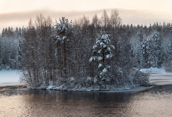 Northern winter lake with trees on island, open water surface