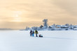People traveling over frozen lake at beauty sunset, cold weather