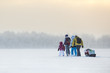 Group of people traveling over ice of lake through winter