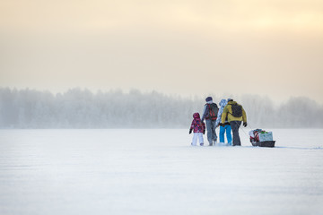 People travel through the blizzard on frozen lake at winter