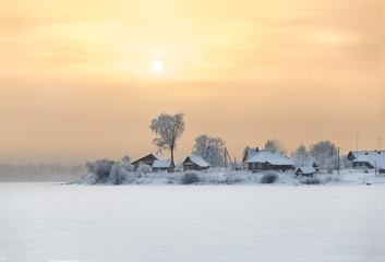 Winter sunset over village on frozen lake shore