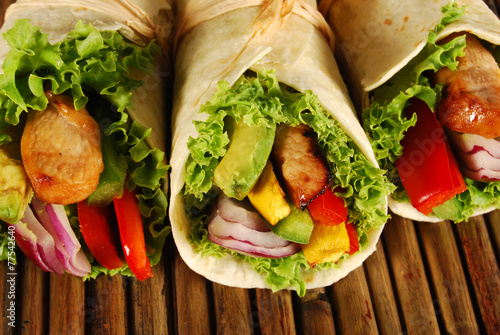 Several chicken wrap sandwiches on mat