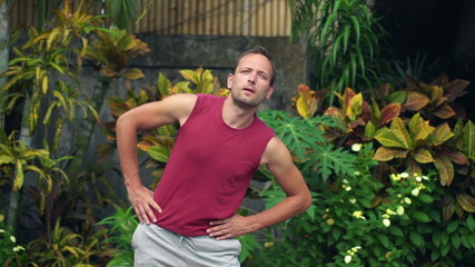 Young man exercising, doing hip circles in garden