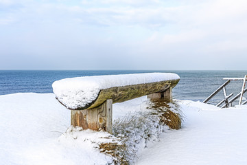 wooden bench covered with snow on the shore of the Baltic Sea