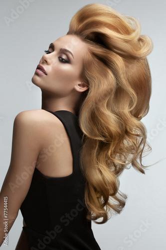 Haarvolumen. Portrait der schönen Blondine mit dem langen gewellten Haar.