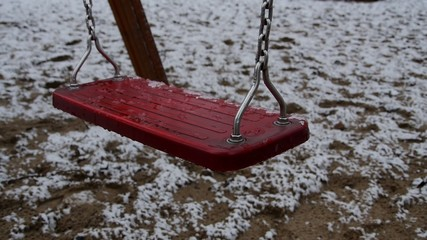 Empty dirty swing during the winter.