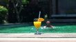 Tropical drink by pool with swimming man