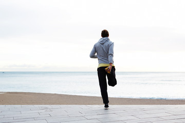 Jogger stretching and admiring beautiful view on the beach