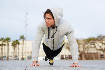 Young athletic man in sweatshirt doing push ups outdoors