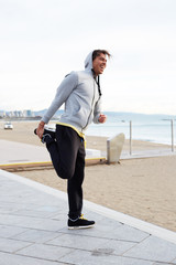 Smiling guy stretching his hamstrings before a run outdoors
