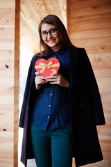 Smiling woman holding red hear gift box on Valentine's Day