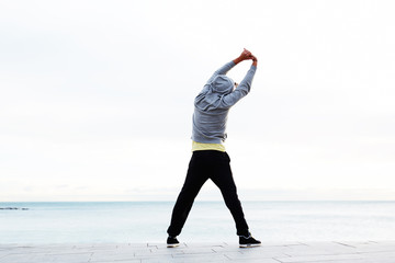 Athletic man doing warm up standing next to the beach