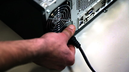 Close shot of a anonymous man plugging in a personal computer
