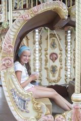 Ten-year girl riding a classic French carousel.