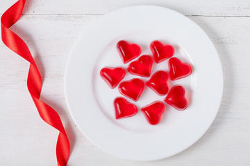 Heart shaped red jelly candies on white dish with ribbon on vint