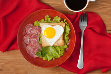 Concept of healthy breakfast or lunch - fried heart-shaped egg