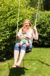 Mutter schaukelt mit Kind im Garten
