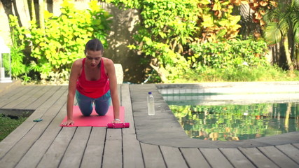 Young woman doing push-ups on mat in garden by swimming pool