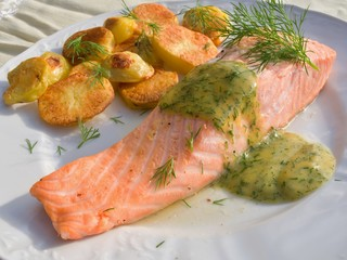 Poached salmon steak with baked potatoes and mustard sauce
