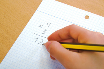 Child doing a math multiplication as homework.