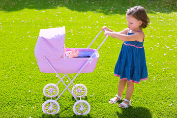 Toddler kid girl playing with baby cart in green turf