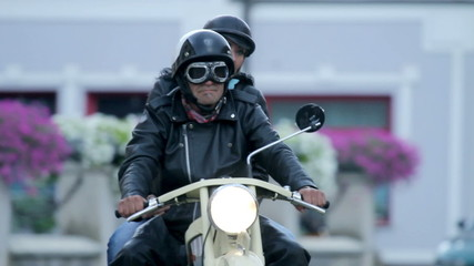 Close up on man and woman driving retro motorcycle through town
