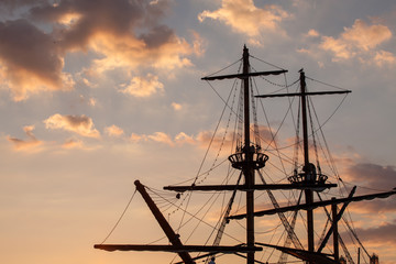 Masts of a pirate ship on sunset