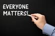 Writing the phrase Everyone Matters on a blackboard