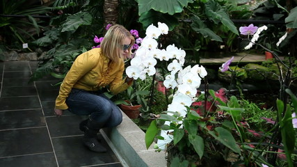 Pretty woman smelling beautiful orchid's blossom in a greenhouse