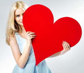 Cute blond girl hiding behind the heart