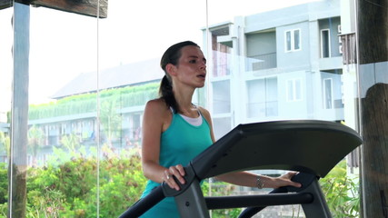 Young, pretty woman running on treadmill in gym