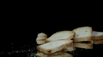 Pieces of bread falling and crumbling on reflective surface