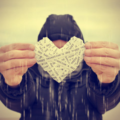young man swhoing a heart under the rain, with a filter effect